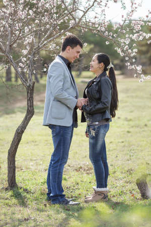 russian ethnicity: Attractive couple in blossoming park. Asian girl and european guy standing against of blossoming almond tree