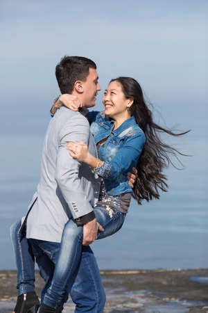 eastern european ethnicity: Attractive couple at the sea. European guy carrying  his asian girl
