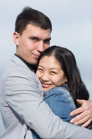 in the open air: Attractive couple on open air. European guy embracing Korean girl