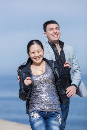 eastern european ethnicity: Attractive couple running along of pier. European guy catches his asian girlfriend