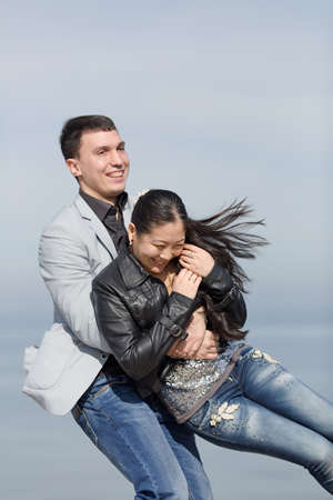 eastern european ethnicity: Attractive couple on pier. European guy catches his asian girlfriend Stock Photo
