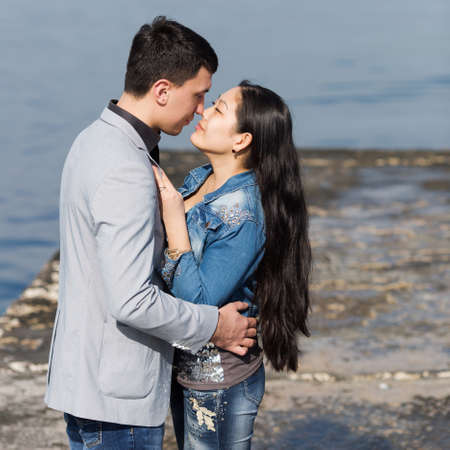 eastern european ethnicity: Attractive couple kissing against of sea. Asian girl and european guy kissing on concrete pier Stock Photo