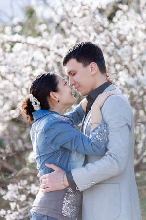 eastern european ethnicity: Attractive couple in blossoming park. Asian girl and european guy kissing against of blossoming almond trees Stock Photo