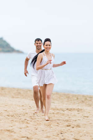 eastern european ethnicity: Barefoot couple on sand seashore in cloudy day. Young man in white shorts and T-shirt catches young woman in white sundress on sand beach