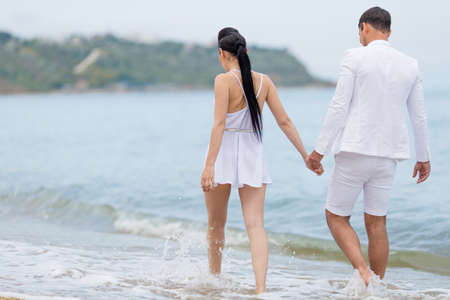 water's edge: Couple on seashore in cloudy day. Attractive couple in white walking along waters edge, rear view Stock Photo
