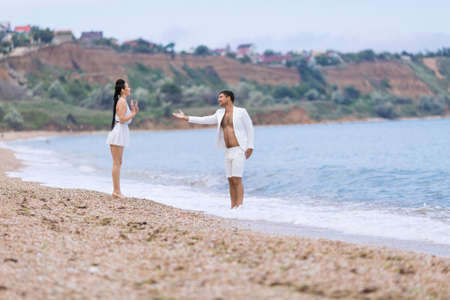 waters edge: Couple on seashore in cloudy day. Guy and girl in white talking at waters edge Stock Photo