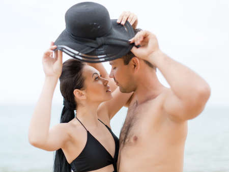 eastern european ethnicity: Couple on seashore in cloudy day. Attractive young couple in black swimwear posing with one for two hat Stock Photo