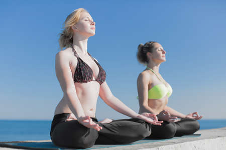 Girls doing yoga outdoors. Two attractive young women meditating on open air