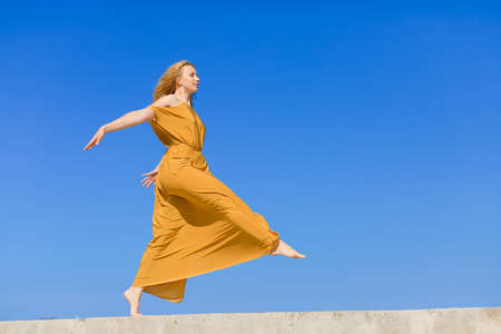 eastern european ethnicity: Girl against the sky. Barefoot young woman in gold-colored long dress running with arms outstretched Stock Photo