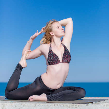 Young woman exercising outdoors. Attractive woman in swimwear doing yoga on open air.