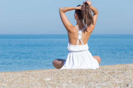 Girl at the sea. Young woman in white sits on pebble seashore and correcting her hairstyle, rear view