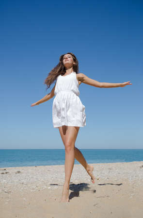 loose hair: Girl running along seashore. Barefoot young woman in white dress skips on sand seashore Stock Photo
