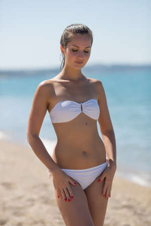 Girl at the sea. Attractive girl in white bikini standing on seashore looking down