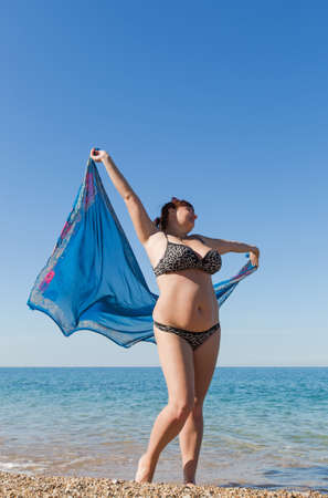 Overweight middle aged woman at the sea. Overweight middle-aged woman with pareo walks along seashore