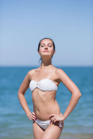 Girl at the sea. Attractive young woman in white bikini stands with arms akimbo against the sea with eyes closed