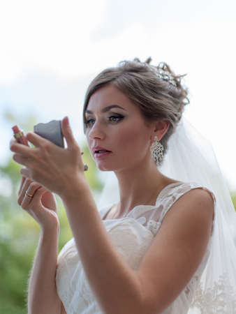 renders: Portrait of bride. Attractive young bride in sleeveless wedding dress looks in mirror and corrects makeup