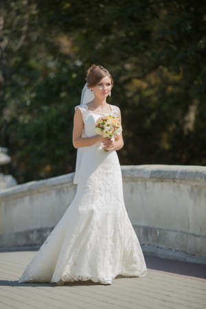Portrait of bride with bouquet on bridge. Attractive bride posing with bridal nosegay on open air Stock Photo