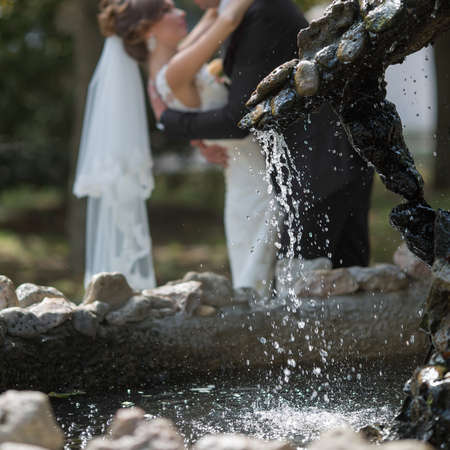 newly wedded couple: Just married in the park. Newly wedded kissing behind fountain. Focus on foreground