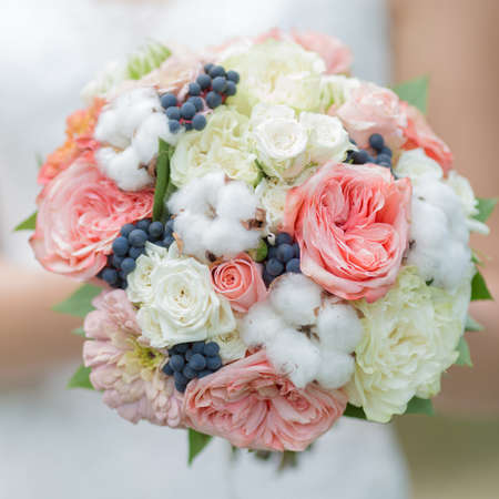 mixed marriage: Bridal bouquet. Nice nosegay with flowers of cotton in hand of bride. Square composition