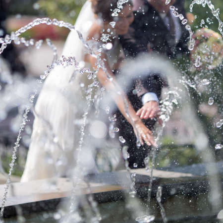 square composition: Newly wedded behind fountain. Hands of newly wedded with wedding rings on their fingers under running water. Square composition
