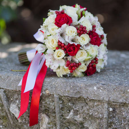 Bridal bouquet. Nice nosegay with white and red tape on concrete wall in the park. Square composition