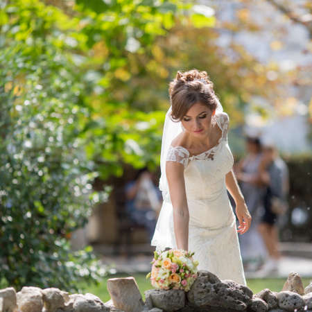 Young bride in the park. Bride picking up bridal nosegay looking down Stock Photo