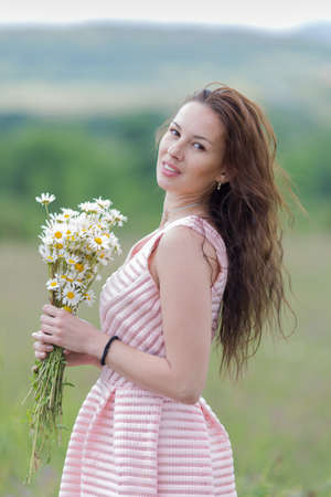 loose hair: Portrait of girl with loose hair outdoors. Attractive young woman with bouquet of chamomiles smiling looking at camera on open air