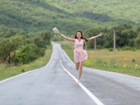 Girl on the asphalt road. Barefoot girl with chamomile bouquet running along road after rain with arms outstretched