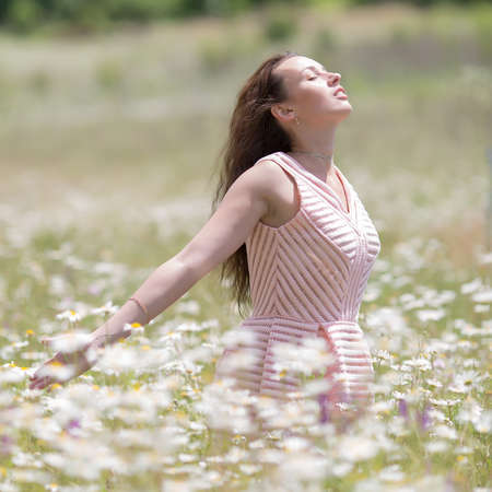 square composition: Girl in chamomile field with arms outstretched. Young woman in pink sleeveless dress walks on meadow of chamomile, square composition