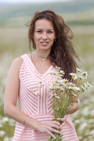 loose hair: Portrait of girl with loose hair outdoors. Attractive young woman with bouquet  chamomiles smiling looking at camera on open air