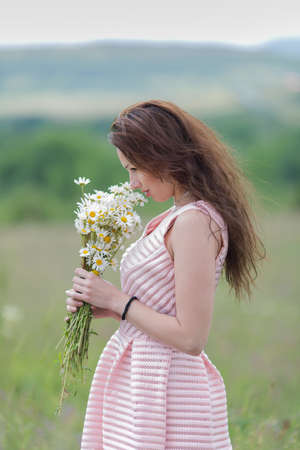 loose hair: Portrait of girl with loose hair outdoors. Attractive young woman sniffs bouquet of chamomile on open air