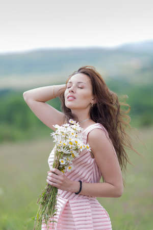 loose hair: Portrait of girl with loose hair outdoors. Attractive young woman with bouquet of chamomile on open air