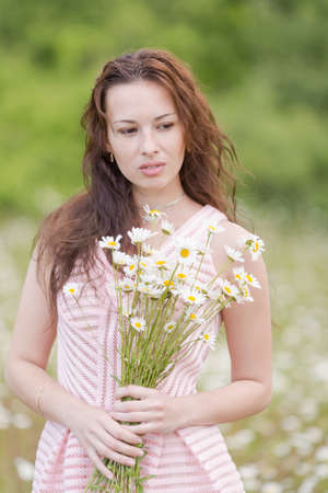 loose hair: Portrait of girl with loose hair in chamomile field. Attractive young woman with bouquet chamomile posing on meadow of chamomiles Stock Photo