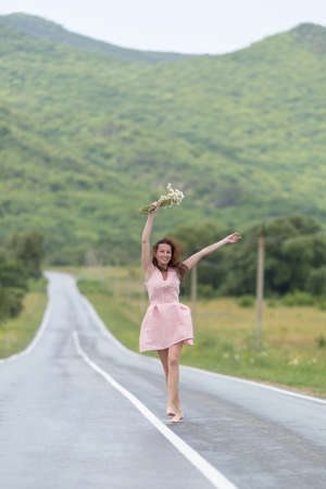 Girl on the asphalt road. Barefoot girl with chamomile bouquet runs along dividing line on wet road after rain Stock Photo