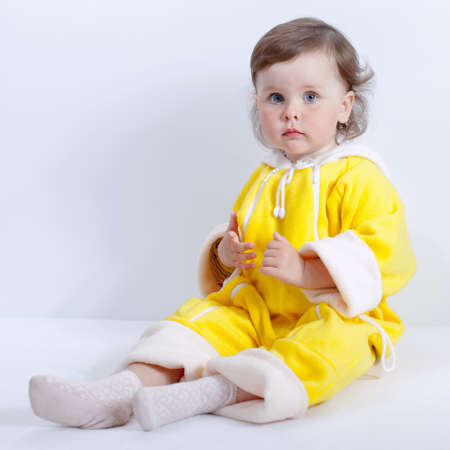 Baby posing in studio on white background. Portrait of charming baby in yellow baby rompers with hood, square composition Stock Photo