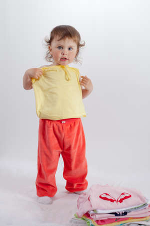 try on: Baby playing in studio on white background. Charming baby in red trousers try on clothes