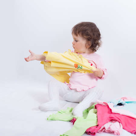 Child puts yellow blouse on. Charming baby playing with clothes in studio on white background