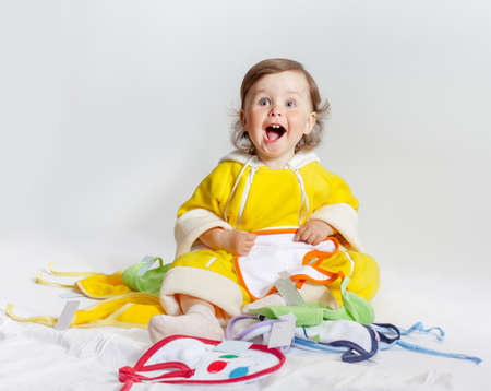 chooses: Baby playing in studio on white background. Charming baby in yellow rompers chooses bib