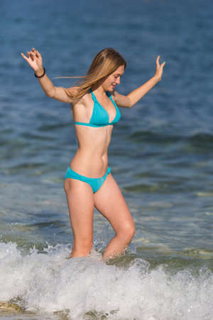 Girl with arms raised goes in sea. Attractive young woman in blue bikini walks in water with arms outstretched