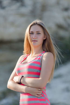 russian ethnicity caucasian: Waist up portrait of girl on open air. Attractive young woman in striped dress posing with hands on stomach looking at camera