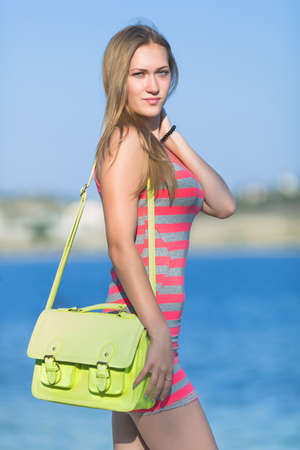 Portrait of girl with loose hair on open air. Attractive young woman in striped dress and yellow bag posing on beach looking at camera Stock Photo