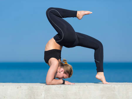 Athletic girl on seafront. Young sportswoman doing exercises against the sea Stock Photo