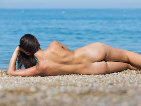 Meisje bij de zee. Naakte jonge vrouw ligt op de kust, die gestutte het hoofd een hand