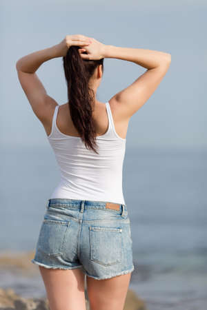 Girl at the sea. Attractive young woman in white tank top adjusts her hairstyle, rear view