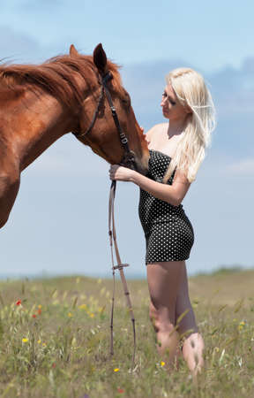 Blonde woman stroking gelding. Young blonde woman in polka-dot dress with brown horse