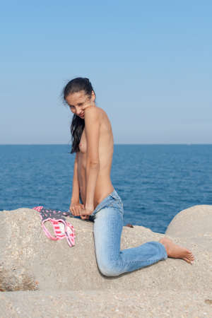 Very slim girl posing on groyne against the sea. Topless young woman in jeans sits legs apart on concrete construction and winks looking at camera