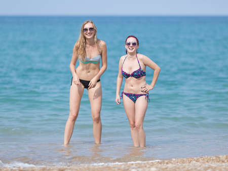 Two girls on the beach. Two young women in bikini and tinted sunglasses standing in sea water and laughing looking at camera