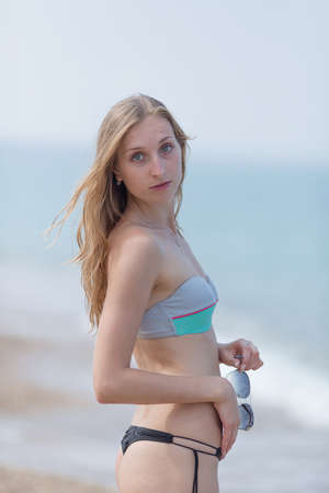 Girl at the sea. Portrait of young woman in bikini on seashore Stock Photo