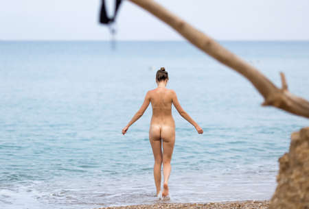 Skinny-Dipping. Naked young woman enters the sea in cloudy day, rear view