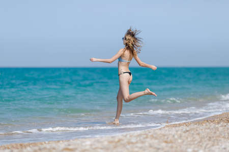 over the edge: Girl on the beach. Tall slim young woman runs in direction of the sea Stock Photo
